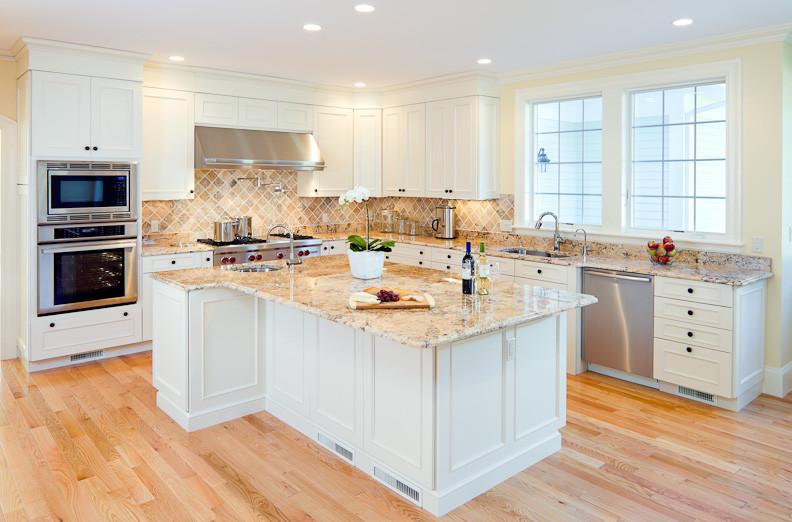 white cabinet granite countertop beige tiled backsplash light hardwood floor stainless steel appliances