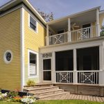 White Painted Railings Idea For Upper Porch Small Mid Size And Rounded Exterior Windows With Glass Panels Lower Exterior Staircase Made Of Wooden Yellow Siding Wall Exterior
