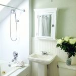 white small master bathroom with white bahttube, white cabinet mirror, white sink, white toilet, white chandelier