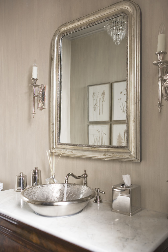 wood cabinet, silver bowl sink, steel faucet, silver framed mirror, two sconces