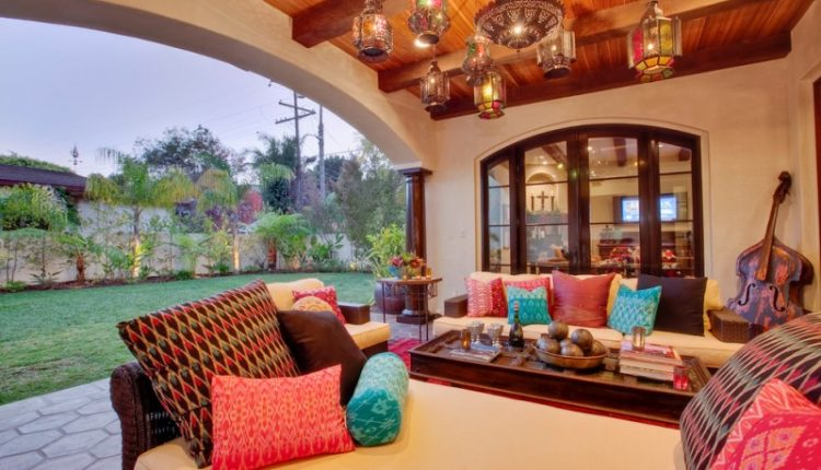 wood ceiling beige sofa wooden table colorful pillows moroccan pendant lamps spaious archway