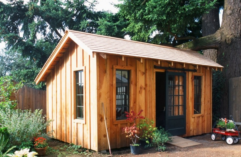 wood color shed with black framed glass windows sliding barn door