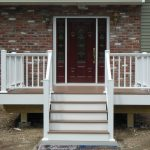 Wooden Railing Idea With White Finishing Original Bricks Exterior With Dark Red Front Door With Art Glass Panel And White Door Trims