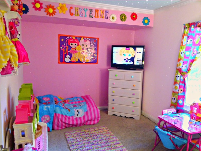 Lalaloopsy girls themed wall painting idea in pink corner storage with TV set on top grey area rug pink & blue bed comforter pink & blue table and chair fluffy and colorful area rug