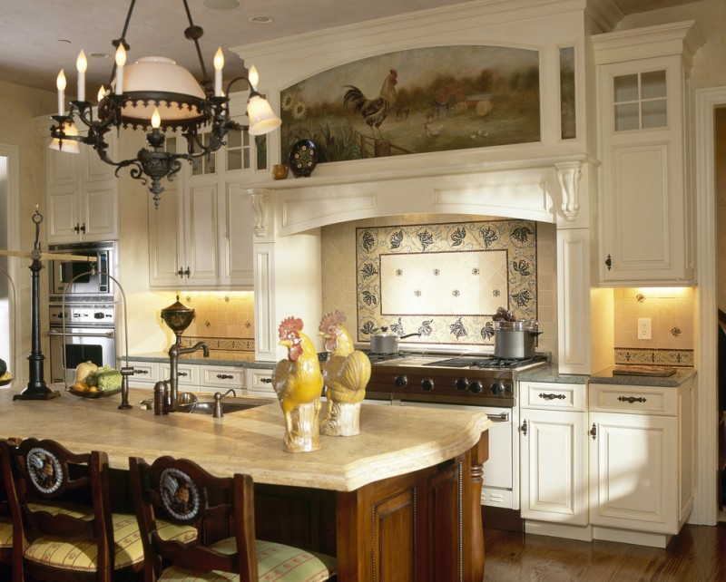 Victorian kitchen with brown island white top, white cabinet grey marble top silver sink, tile blacksplash, rooster mural mantle, white victorian candhelier, silver stove oven