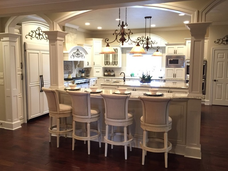 Victorian kitchen with white island white marble top, white cabinet white marble top, white wall mounted cabinet, white cipboard, white victorian chandelier, silver stove oven