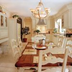 Victorian kitchen with white marble flooring, white wooden chair, brown top table with white wooden legs, white cabinet with white top, white wall mounted cabinet, white cupboard,
