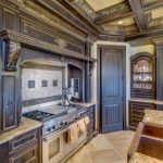 Victorian Kitchen With Worn Out Wooden Cabinet, Brown Marble Top, Brass Sink, Silver Stove Oven, Tile Backsplash