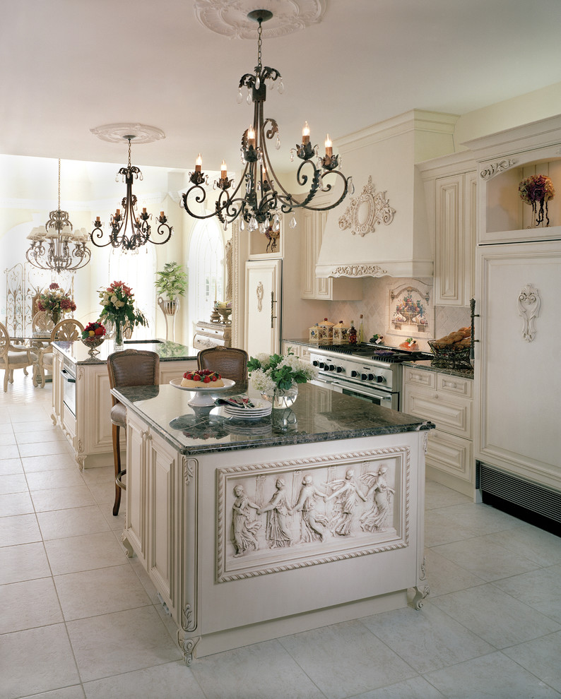 White Victorian kitchen with relief island with grey marble top, white wooden cabinet, white chimnet, silver oven and stove, white tile flooring, black rustic chandelier,