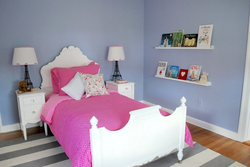 antique style girls room with blue painted walls white bed frame with headboard white bedside tables white floating shelving units monochromatic area rug under bed medium toned wood floors