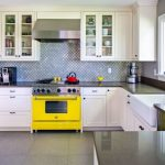 arabesque backsplash kitchen big windows yellow pop stove wall cabinets faucet sink traditional room