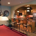 bar near a game area with arch ceiling, wooden bar counter, wooden kitchenette, iron stool with brown cushion, bowl pendant