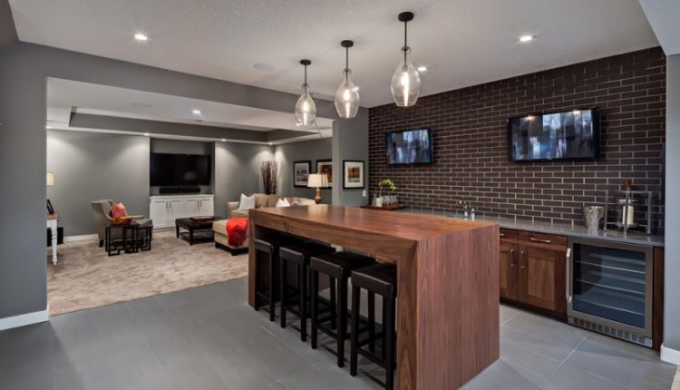 bar with simple thick wood table, brick backsplash, grey tile, wooden cabinet with metallic counter, dark wood leathered stools, clear glass pendant
