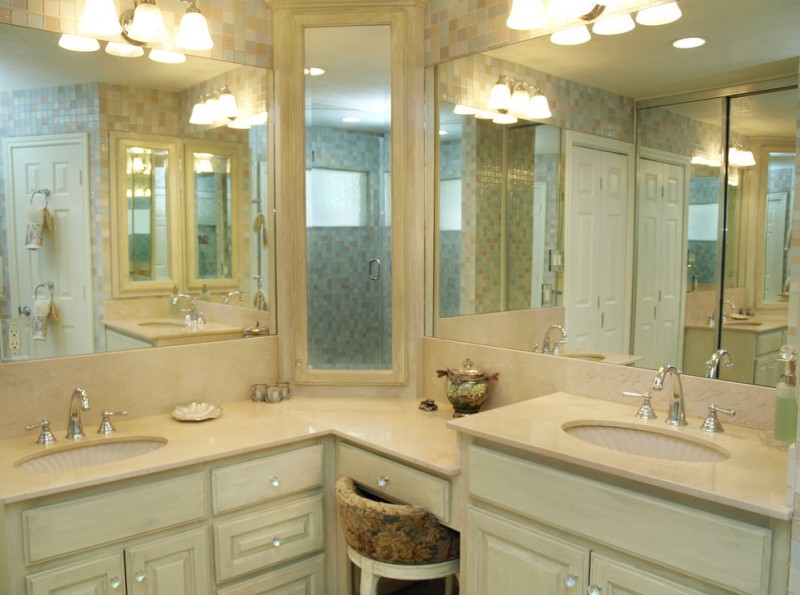 bathroom with L shaped vanity in cream, cabinetry in cream, sconces, sink on both ends, mirror along the vanity