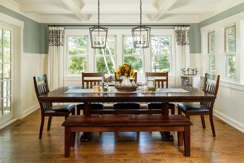 bench dining room table wood floor chairs chandeliers flowers windows traditional style table cloth curtains