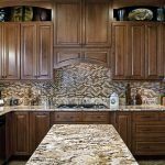 brown granite countertop brown tiled backsplash wood cabinet kitchen island stove top