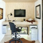 brown hoem office with light brown flooring up to the wall up front, table, wall mounted screen, black chair, grey cabinet, painting, cow skin patterned rug