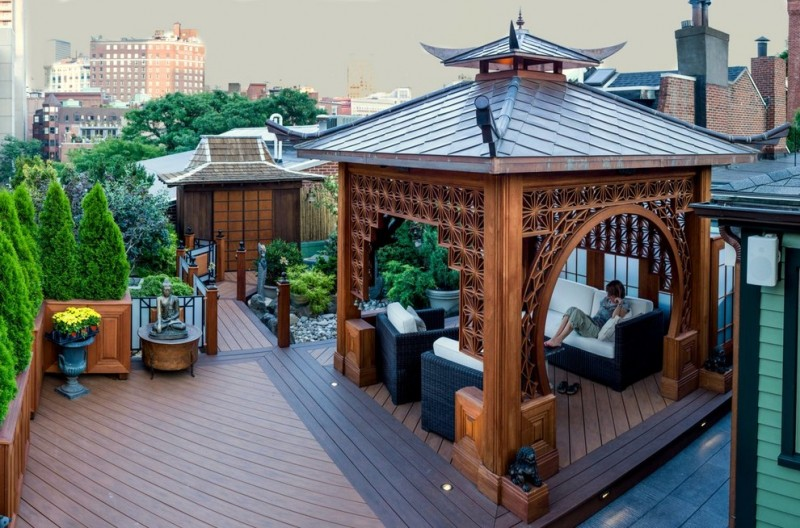chinese wooden gazebo with dark metal roof, black rattan chairs with white cushion