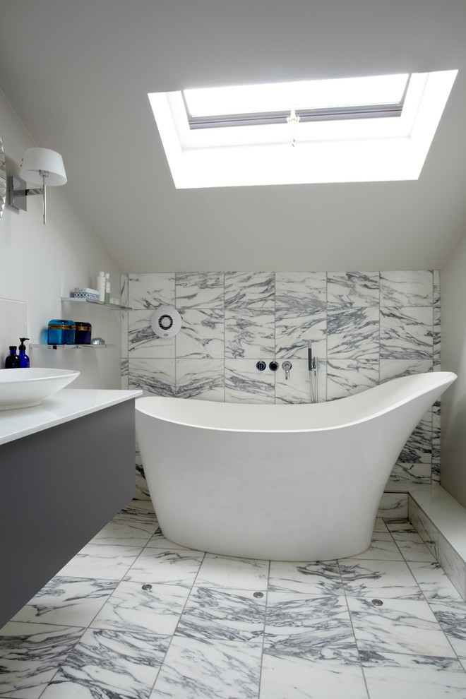 classic bathroom with white curvy tub, white grey tiles wall and floor, grey cabinet with white counter top and sink