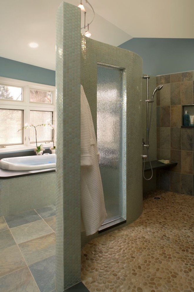 contemporary bathroom with natural look tiles in bath area and interlocking pebbles flooring in shower area
