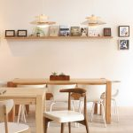 Contemporary Dining Room Idea With Pale Wood Dining Tables And Wood Chairs With White Accent Single Floating Wood Ledge For Standing Pictures And Books
