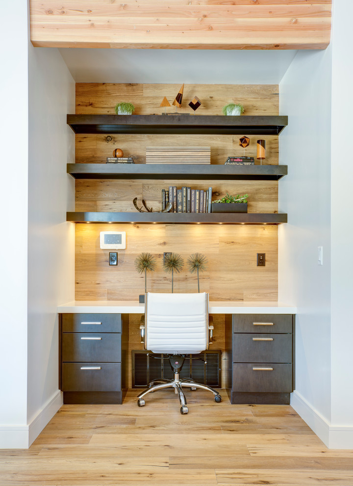 corner home office with wood flooring up to one side of the wall while two others side in white paint, mounted sheleves up front, black cabinet with white top, white chair