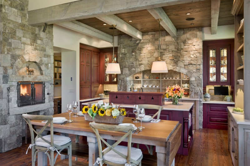 country eat in kitchen remodel with stone walls fireplace hardwood dining table shabby wood dining chairs purple kitchen island purple cabinets white countertop dark wood floors