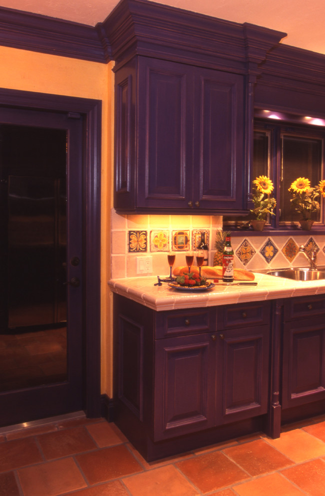 custom Mediterranean kitchen idea with deep purple cabinets printed tiles backsplash clay burnt tiles floors