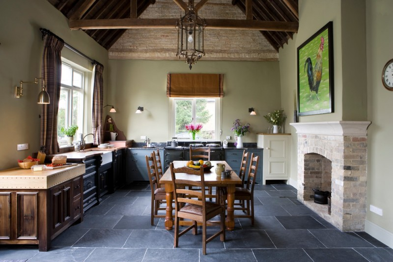 dark wooden kitchen table chairs cabinets black charcoal floor tiles cabinets brick stone roof  stone fireplace brass kitchen appliance pendant light pale green wall
