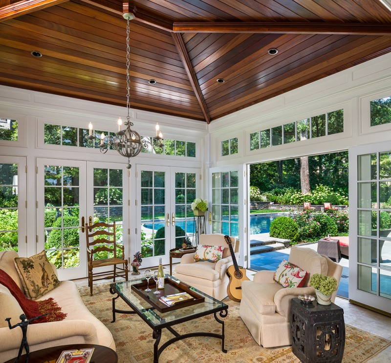 four season porch brown wood ceiling traditional sunroom romantic style white couch arabian rug swimming pool view