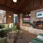 four season porch green comfy couch traditional fireplace ethnic rug wooden ceiling stone wall unique table