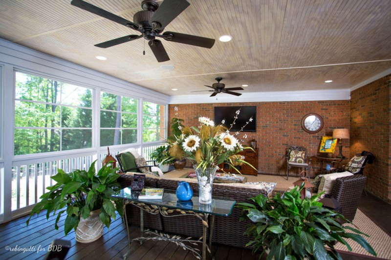 four season porch rustic design fresh plants black ceiling fan brick design wall traditional rug