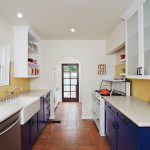 galley kitchen navy blue cabinets stainless steel appliances farmhouse sink yellow backsplash white raised cabinet terracota floors
