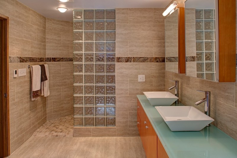 glass brick wall cream bathroom tiles cabinet light blue countertop rectangular sink mirror brass tap