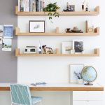home office are with white wall, wooden mounted shelves, white wooden table with white wooden cabinet under, blue chair