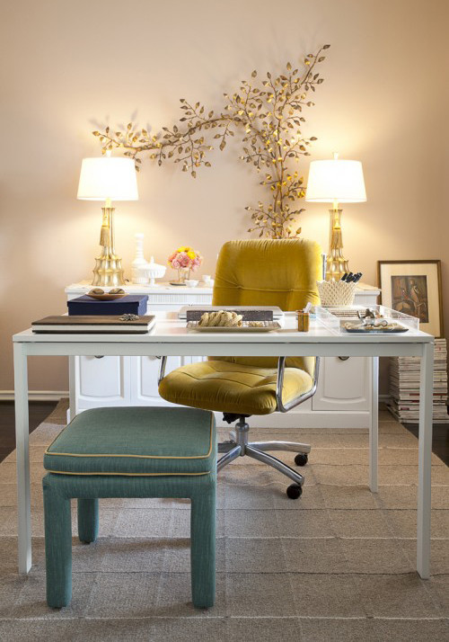 home office with cream wall, white table, white cabinet, yellow chair, green ottoman, two table lamps. golden branch