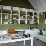 Home Office With Vaulted Ceiling, Green Wall, Grey Flooring, Green Couch, White Wall Mounted Wooden Shelves, White Wooden Cabinet, White Table With Glass Top, Brown Chair