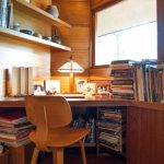 home office with wood covering walls with wooden table, chairs, and shelves