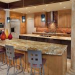 ice brown granite coutertop metal stools light cabinet dark brown tiled backssplash stainless steel appliances