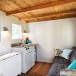 kitchen in tiny house with dark grey sofa, sink, white cabinet, blue shelves, white wall