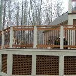 lattice skirting for high level deck black wrought iron railing system supported by wood rail posts and solid concrete pillars