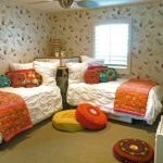 Light Beige Wall Garnished With Colorful Butterflies White Bed Comforter Orange Blanket Colorful Round Accent Pillows Corner Bench Behind Twin Beds