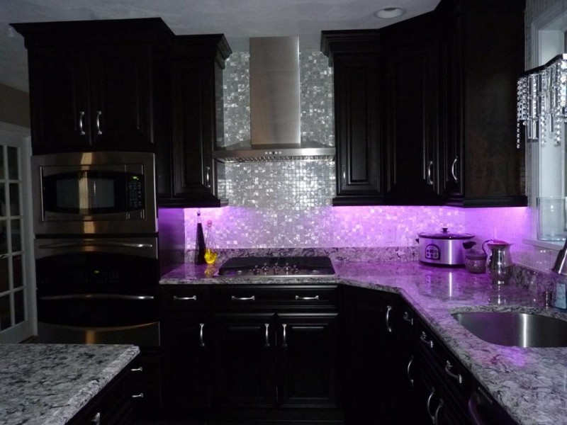 luxurious and glamourous kitchen idea with shiny purple ambiance glowing silver toned backsplash black painted cabinets marble countertop stainless steel appliances
