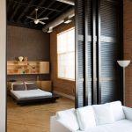Mountain Style Wood Loft Bed Design Hardwood Floors Wood Shelves At The Back Of Bed Dark Grey Brick Walls Ceiling Fan
