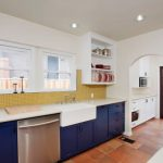 Navy Blue Kitchen Cabinets Stainless Steel Appliances Farmhouse Sink Yellow Backsplash White Raised Cabinet Terracota Floors