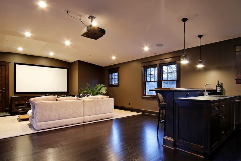 nicely designed basement floors hardwood floor sofa pillows drawers lights projector home theater windows hanging lamps