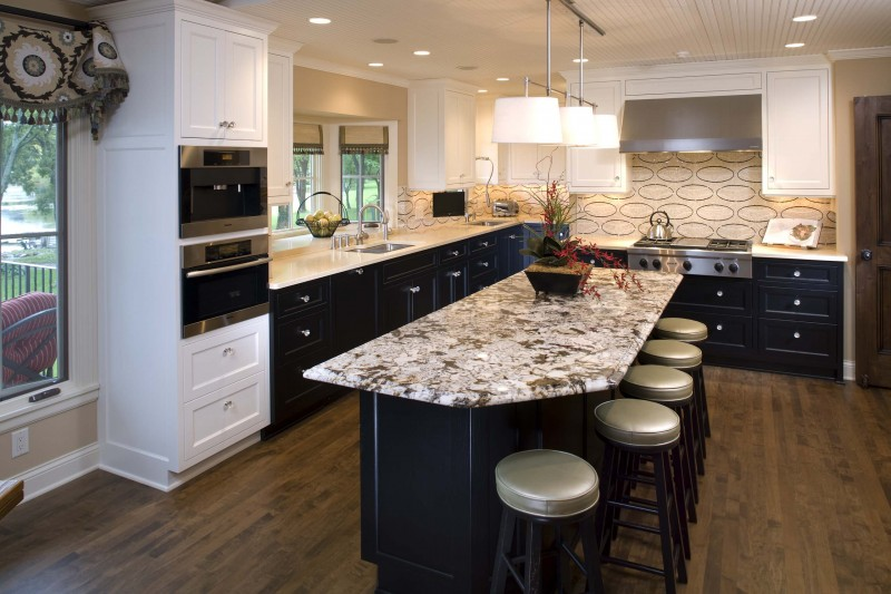 oval shaped backsplash exodus white granite countertop black island white cabinet black cabinet white pendant lights wooden floor