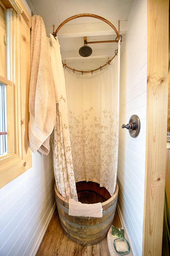 rustic bathroom with woodbrown woodenn flooring, white wooden panel wall, wooden round bathtub with shower, white curtain