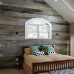 rustic bedroom with one side wall of reclaimed wood in a vaulted ceiling room