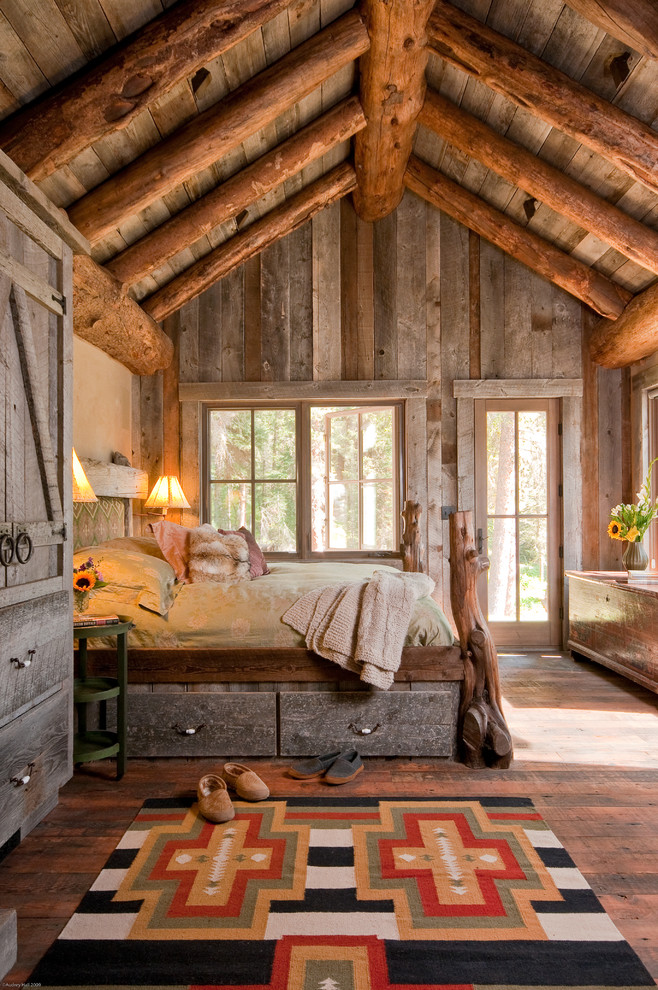 rustic mud wood interior bedroom bed pillow carpet door windows logs underbed storage lamps cupboard
